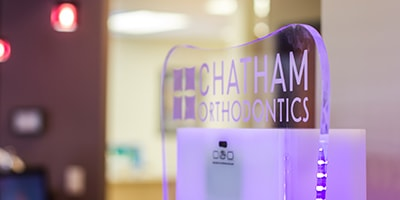 Chatham Orthodontics waiting room with their logo