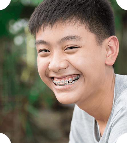 A teenager smiling with braces because of orthodontics Chatham NJ