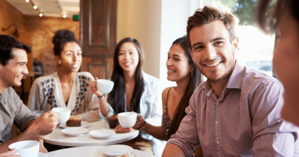 group of people smiling together getting coffee