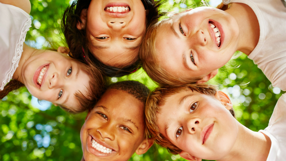 group of kids smiling together in a circle