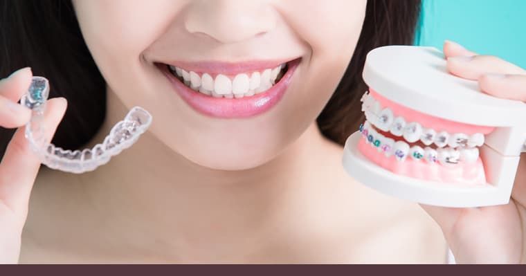 Lady holding Invisalign aligners and braces, deciding which one to choose.