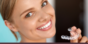 woman smiling holding an invisible retainer